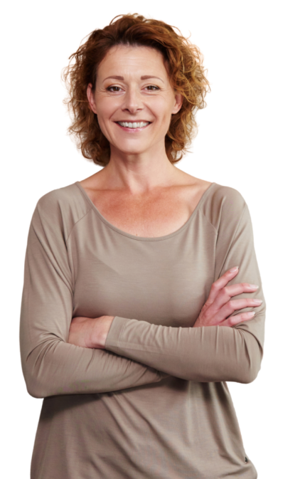 older-woman-smiling-with-arms-crossed-by-wall-PDB2L4D-removebg-medium-605x1024